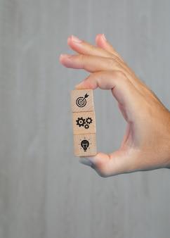 Concepto de negocio en vista lateral de la mesa gris. mano sosteniendo cubos de madera con iconos.