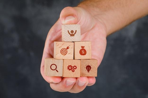 Concepto de negocio en vista lateral de la mesa gris sucio. mano sosteniendo bloques de madera con iconos.