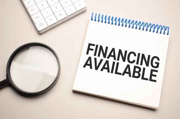 Concepto de negocios y finanzas. sobre la mesa hay una lupa, una calculadora y un cuaderno con la inscripción - financiación disponible