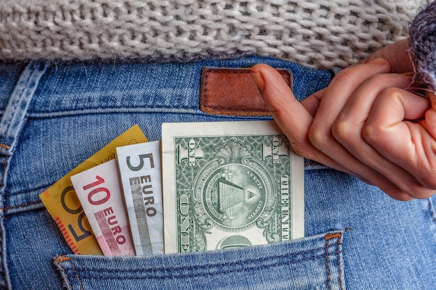 Concepto de negocios, ganancias, viajes y finanzas en internet usd, aud y eur en el bolsillo trasero de blue jeans con mano femenina buscando el dinero