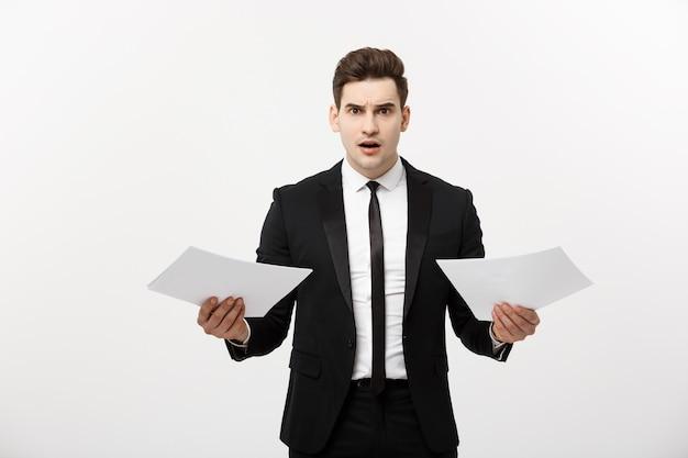 Concepto de negocios, personas, papeleo y fecha límite: apuesto hombre de negocios estresado con papeles y gráficos que muestran una expresión facial impactante con resultado