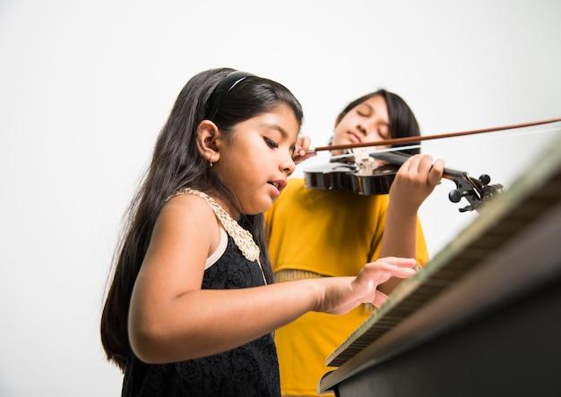 Concepto de niños y música - niñas indias tocando instrumentos musicales como piano, teclado o violín