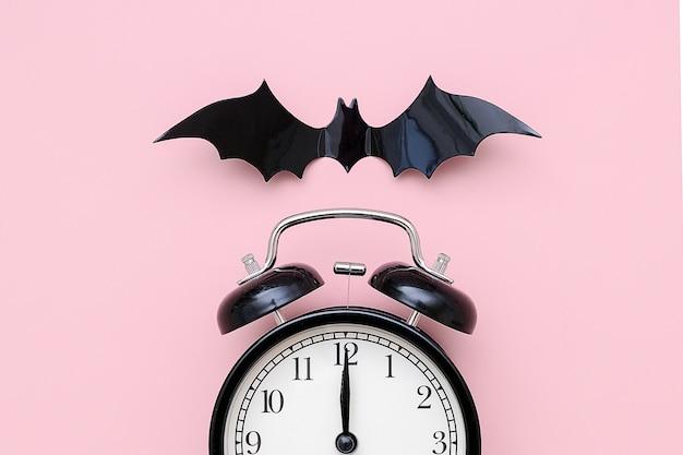 Concepto de la noche de halloween. despertador negro y murciélago volador en rosa