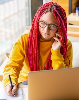 Concepto de nómada digital. chica independiente hablando por teléfono móvil, trabajando de forma remota en la computadora portátil