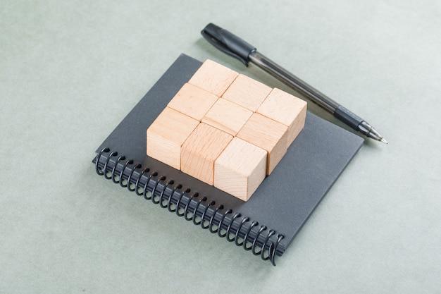 Concepto de notas comerciales con bloques de madera, lápiz sobre la mesa de color salvia vista de ángulo alto.