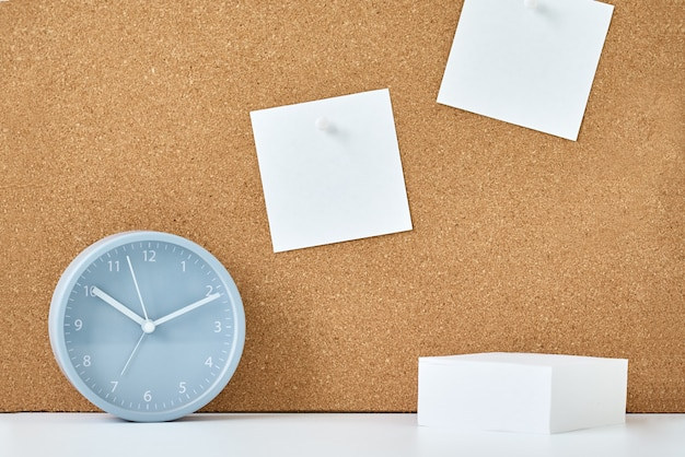 Concepto de notas, objetivos, memorando o plan de acción, notas adhesivas en el tablero de corcho y reloj despertador en la oficina del trabajo o en el hogar