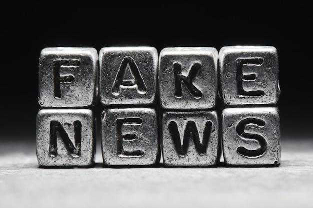 El concepto de noticias falsas. inscripción en cubos 3d de metal aislado en un fondo negro, estilo grunge