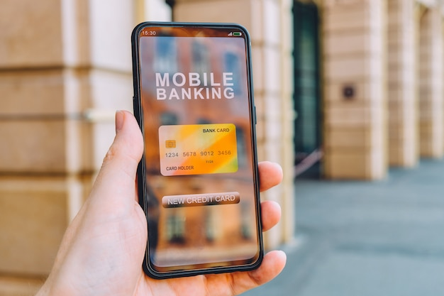 Concepto de una nueva tarjeta de crédito en una aplicación de interfaz de banca móvil para teléfonos inteligentes en la mano