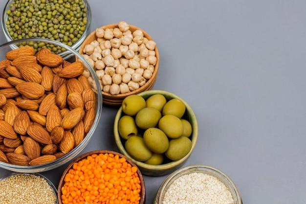 Concepto de nutrición de alimentos saludables. granos de leguminosas semillas nueces aceitunas sobre fondo gris