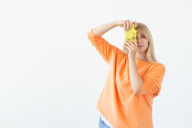 Concepto de ocio y afición del fotógrafo joven mujer rubia con cámara retro sobre fondo blanco con