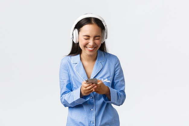 Concepto de ocio, fines de semana y estilo de vida en el hogar. feliz chica asiática en pijama azul, escuchando podcast divertido en auriculares, riendo a carcajadas, mirando videos divertidos en el teléfono móvil, fondo blanco.
