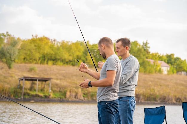 Concepto de ocio y personas. amigos felices con cañas de pescar en el muelle junto al lago.