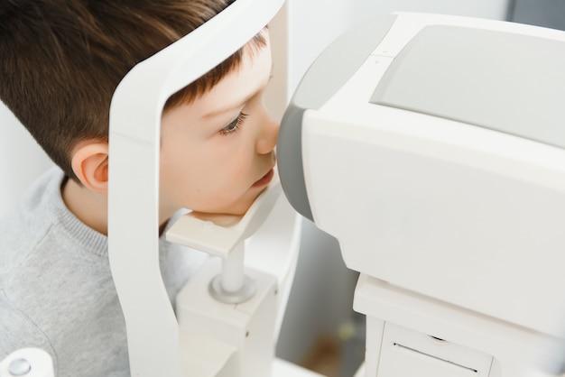 Concepto de optometría. mujer médico óptico optometrista examina la vista del niño en la clínica oftalmológica del ojo