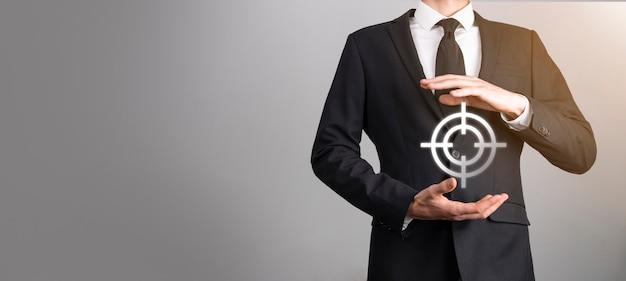 Concepto de orientación con la mano del empresario sosteniendo el boceto de la diana de icono de destino en la pizarra. objetivo objetivo y concepto de meta de inversión.