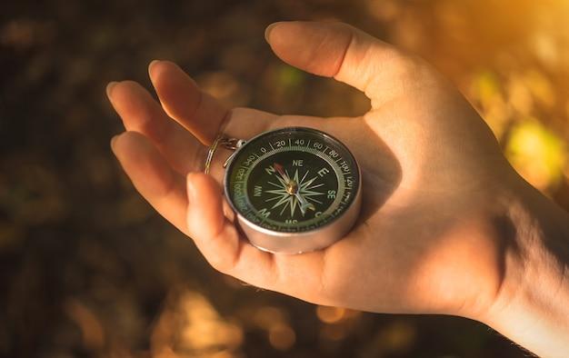 Concepto de orientación a la naturaleza. mano de fenale con brújula en el fondo del bosque