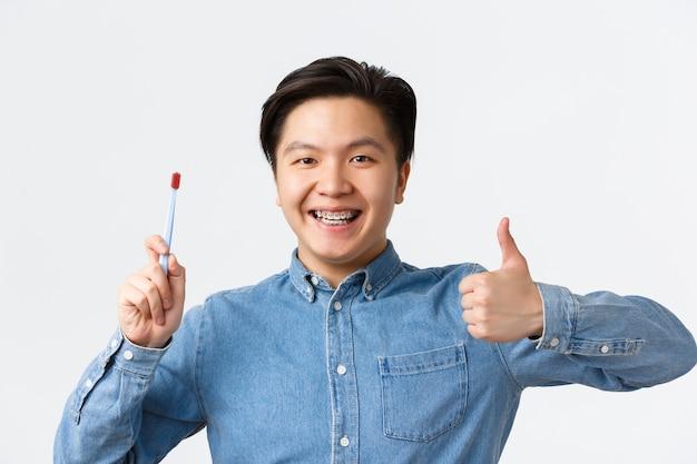 Concepto de ortodoncia, cuidado dental e higiene. primer plano de un hombre asiático satisfecho mostrando el pulgar hacia arriba mientras recomiendo usar cepillo de dientes o pasta de dientes para los dientes con frenillos, sonriendo complacido