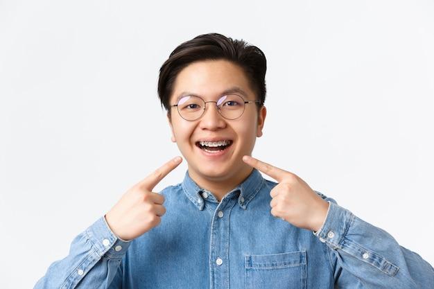 Concepto de ortodoncia y estomatología. primer plano de chico asiático satisfecho, cliente de clínica dental sonriendo feliz y apuntando a sus aparatos dentales, fondo blanco de pie, recomendar calidad.