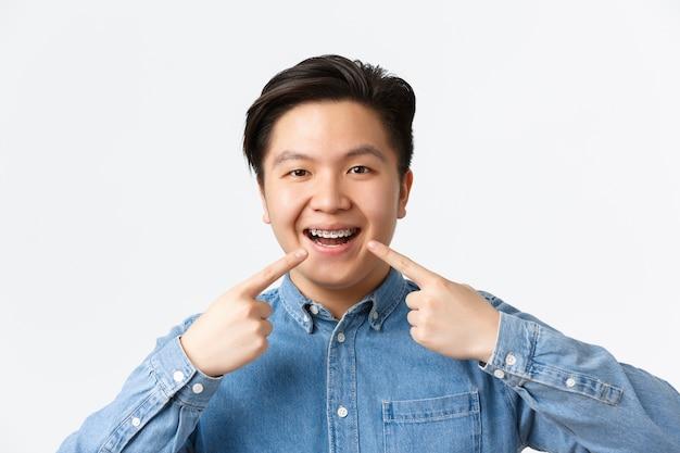 Concepto de ortodoncia y estomatología. primer plano de hombre asiático sonriente feliz señalando con el dedo a los aparatos dentales en los dientes con expresión complacida, recomendar clínica de dentista, pared blanca de pie