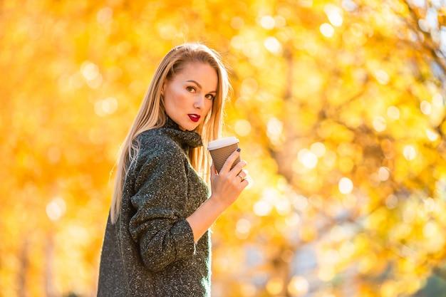 Concepto de otoño - hermosa mujer tomando café en el parque de otoño bajo el follaje de otoño