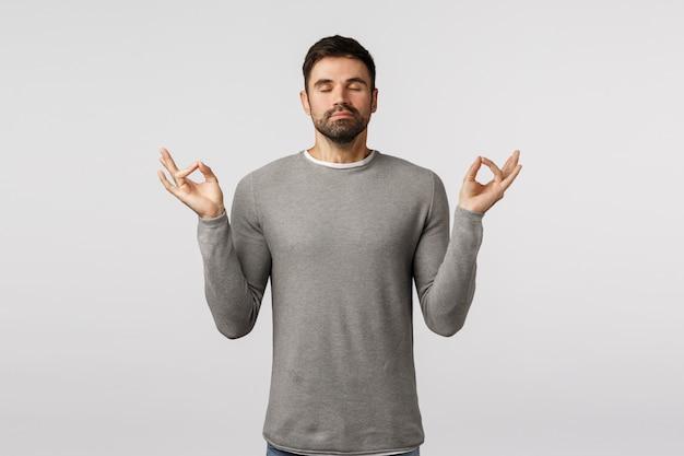Concepto de paciencia, relajación y meditación. tranquilo joven apuesto chico barbudo amplía la mente y el cuerpo, siente zen, levanta las manos con el gesto de mudra, practica respirar yoga con los ojos cerrados