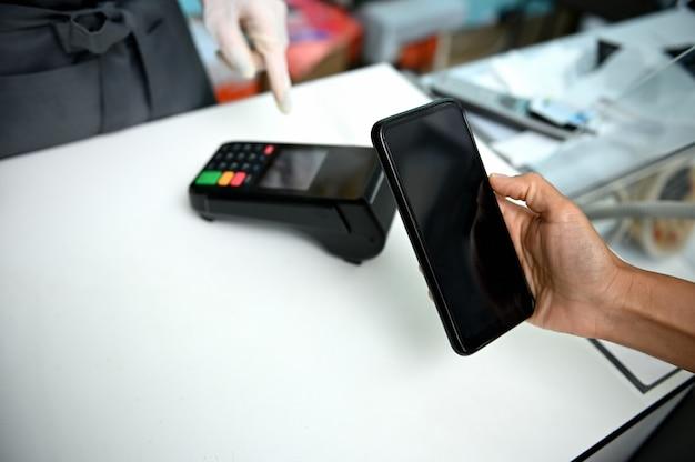 Concepto de pago sin contacto. pagar la factura a través de un teléfono inteligente con tecnología nfc en una tienda de mariscos. cliente que paga a través de un teléfono inteligente utilizando tecnología sin contacto.