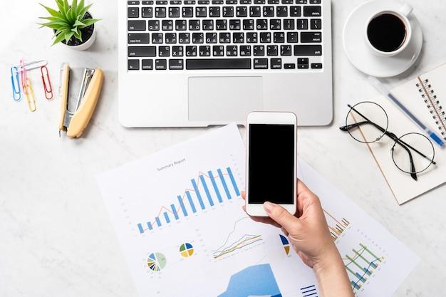 Concepto de pago de facturas en línea, una mujer que usa una tarjeta de crédito simulada y un teléfono celular móvil en el escritorio de oficina aislado sobre fondo de mármol, espacio de copia, vista superior, flatlay, primer plano