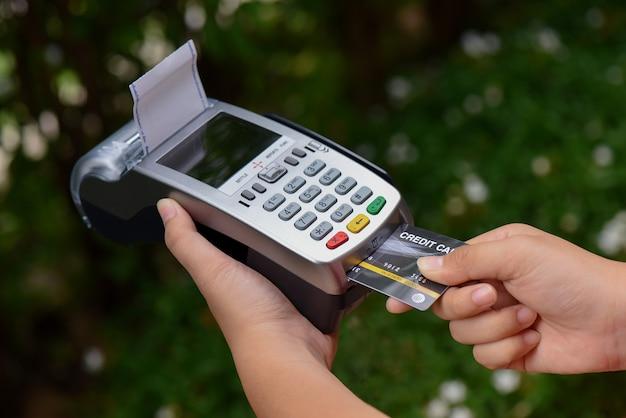 Concepto de pago con tarjeta de crédito. primer plano mano inserte la tarjeta de crédito simulacro con tarjeta en blanco con una máquina de tarjeta magnética