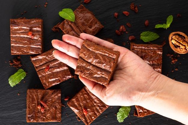 Concepto de panadería casera de alimentos vista superior de brownies orgánicos decorados por dulces en pizarra negra