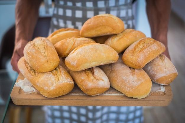 Concepto de panadería y pan recién hecho - hombre adulto de pie con comida - trabajo y trabajador atisan - estilo de vida saludable y estilo de vida alternativo