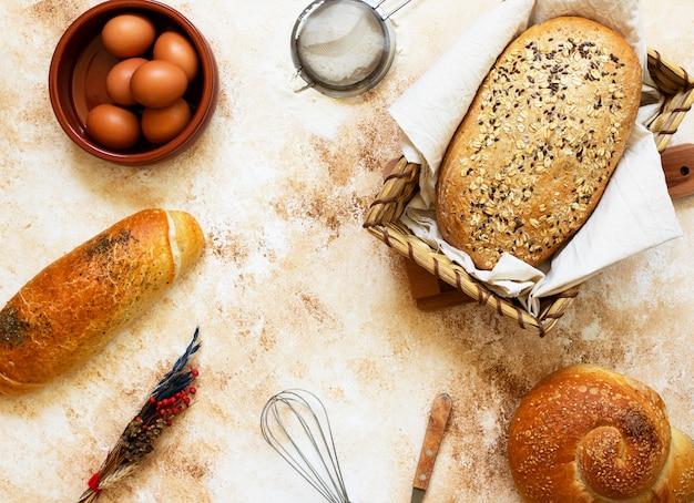 Concepto de panadería. una variedad de diferentes tipos de pan sobre un fondo claro. vista superior (endecha plana). espacio para texto