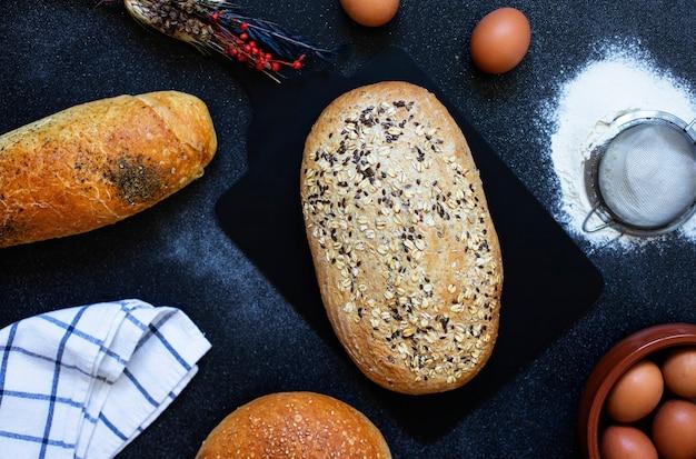 Concepto de panadería. una variedad de diferentes tipos de pan sobre un fondo oscuro. huevos, harina, espigas. vista superior (endecha plana)
