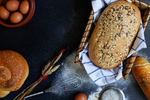 Concepto de panadería. una variedad de diferentes tipos de pan sobre un fondo oscuro. pan en una canasta, huevos, harina, espigas. vista superior (endecha plana). espacio para texto