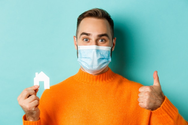 Concepto de pandemia de bienes raíces y coronavirus. primer plano, de, hombre adulto, en, médico, máscara, tenencia, pequeño, casa