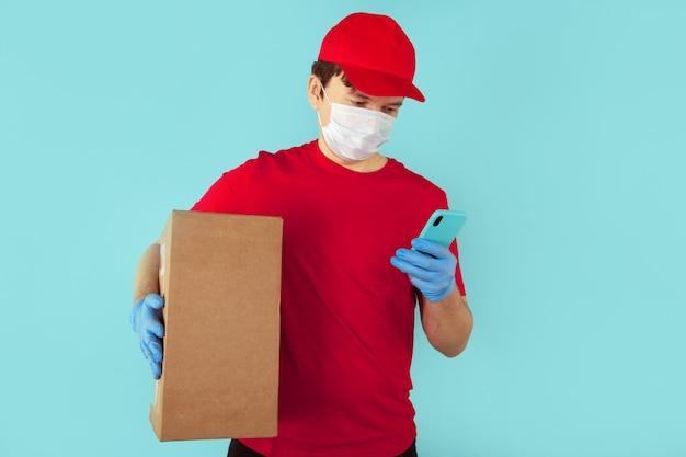 Concepto de paquete de entrega. mensajero en caja roja de la tenencia de t-shurt aislada sobre el azul.