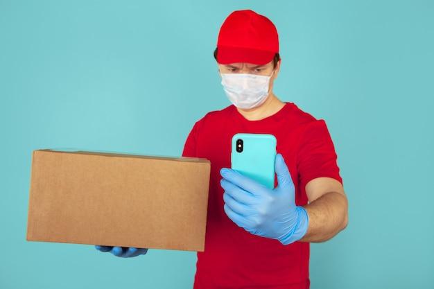 Concepto de paquete de entrega. mensajero en rojo t-shurt con caja sobre el azul.