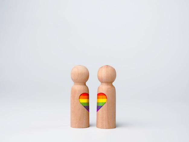 Concepto de pareja lgbt. bandera del arco iris en forma de corazón en dos figuras de madera juntas aisladas sobre fondo blanco. símbolo del orgullo lgbt.