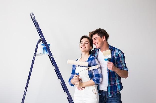 Concepto de pareja de reparación, renovación y amor: mujer joven y hombre haciendo reparaciones con caras felices