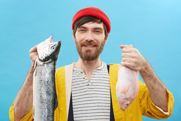 Concepto de pasatiempo, recreación, ocio y actividad. alegre joven pescador sin afeitar o pescador con ropa elegante y colorida sosteniendo dos peces recién capturados, sonriendo ampliamente, sintiéndose orgulloso de su captura