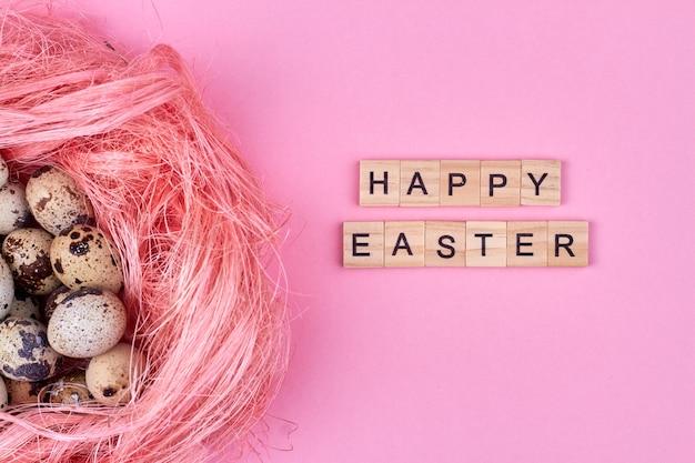 Concepto de pascua feliz. huevo de codorniz rosa y feliz pascua.