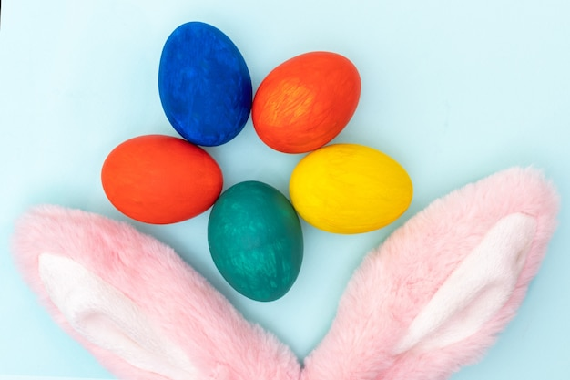 Concepto de pascua feliz. huevos de pascua pintados a mano y orejas de conejo rosa sobre un fondo blanco. tarjeta de pascua minimalista.