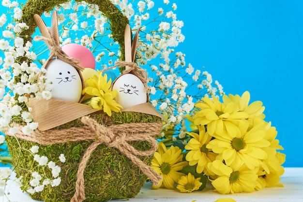 Concepto de pascua. huevos en canasta decorada con flores en azul