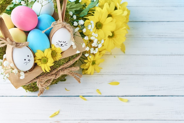 Concepto de pascua. huevos en canasta decorada con flores, espacio de copia