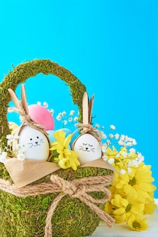 Concepto de pascua. huevos en canasta decorada con flores sobre un fondo azul.