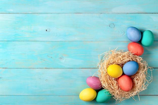 Concepto de pascua. huevos de colores sobre fondo de madera azul con espacio de copia de texto. vista de arriba hacia abajo o plano