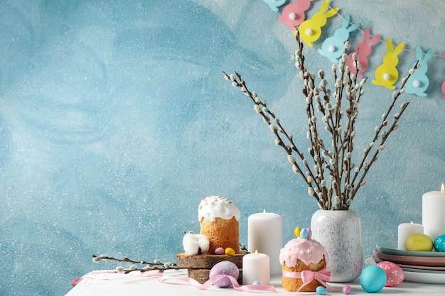 Concepto de pascua con pasteles de pascua y velas en la mesa de madera