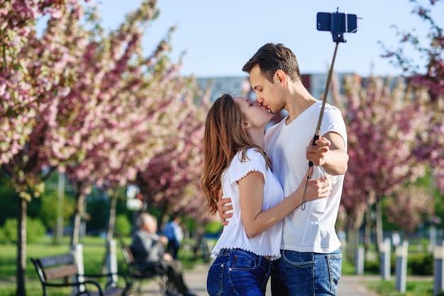 Concepto de pasión y amor. hombre y mujer besándose en el jardín floreciente en primavera.
