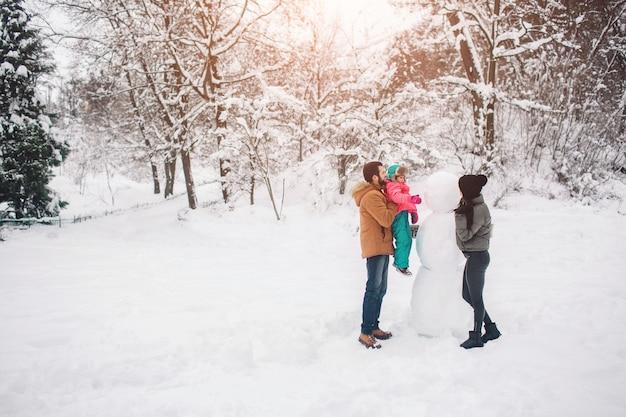 Concepto de paternidad, moda, temporada y personas: familia feliz con niño en ropa de invierno al aire libre