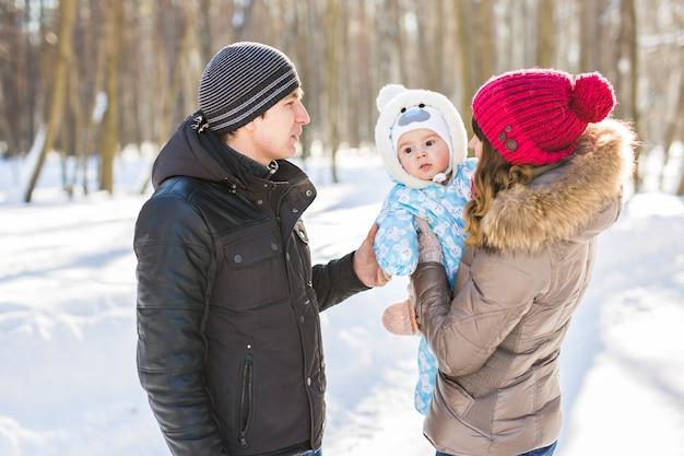 Concepto de paternidad, moda, temporada y personas - familia feliz con niño en ropa de invierno al aire libre.