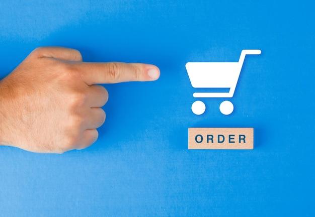 Concepto de pedido con bloque de madera, icono de la cesta de papel en la mesa azul plana. mano de hombre apuntando.