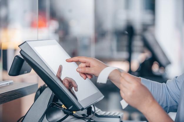 Concepto de pequeña empresa o sevicio, mujer o vendedora en delantal en el mostrador con una caja de efectivo trabajando en la tienda de ropa, pos con pantalla táctil